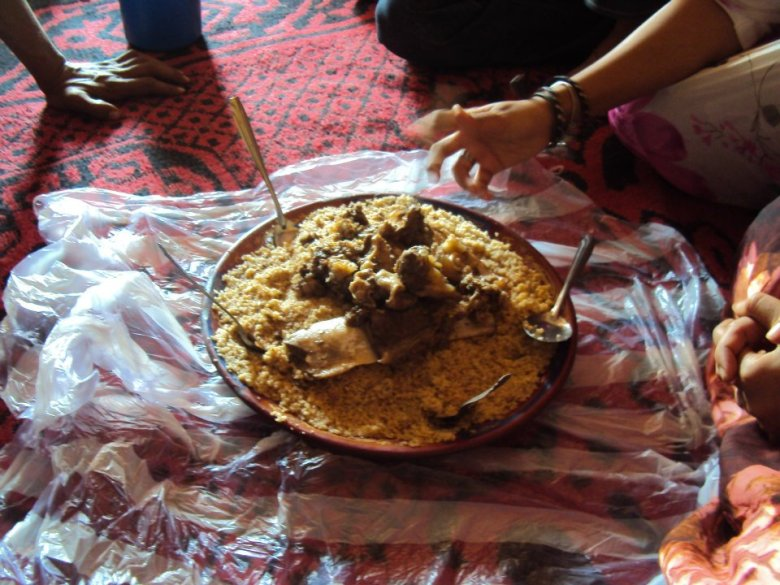 Almuerzo tradicional saharaui: cus-cus con carne de camello, todos comiendo del mismo plato
