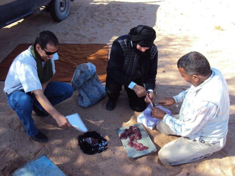 Los hombres del grupo asando la carne de camello para el almuerzo