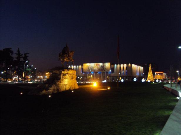 Vista nocturna de la Plaza Skanderbeg y del Museo de Historia Natural. Se ve también la bandera de Albania.