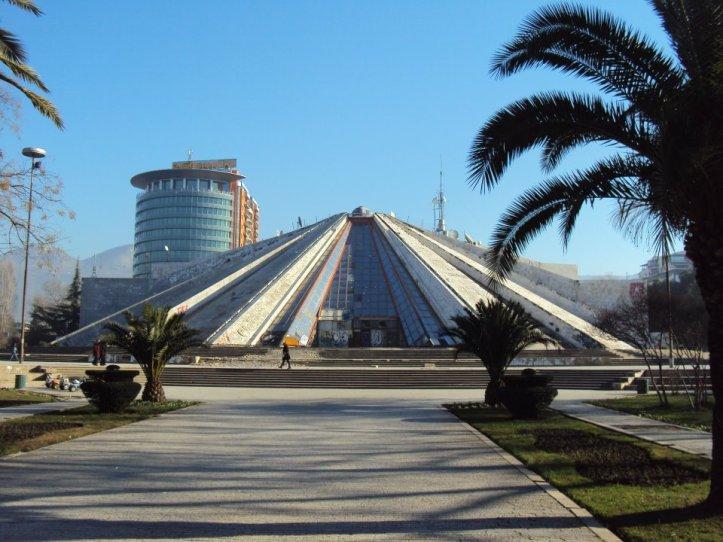 """La pirámide fue construida en 1998 como un museo dedicado al dictador (que además tenía ínfulas de faraón) Enver Hoxha. Diseñada por la hija de Hoxha, Pranvera, el edificio fue el más caro que jamás se haya construido en el país. Luego del colapso del régimen, la pirámide se convirtió en un centro de convenciones y en una discoteca llamada """"La Momia"""". Actualmente está siendo renovada para convertirse en un teatro. Tirana, Albania."""