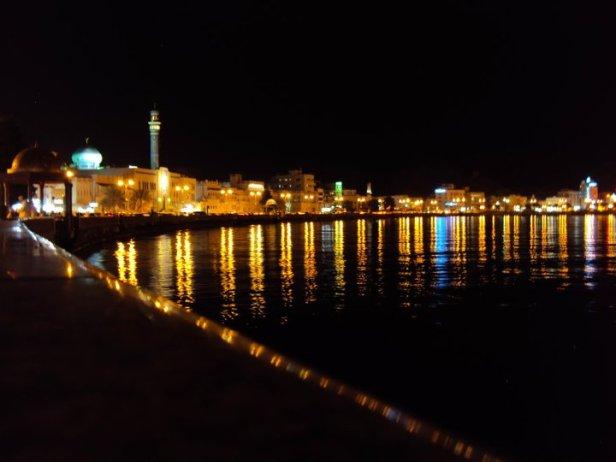 Vista nocturna de la Bahía de Muttrah en el centro de Mascate. A la izquierda se ve el minarete de la Mezquita de Muttrah.