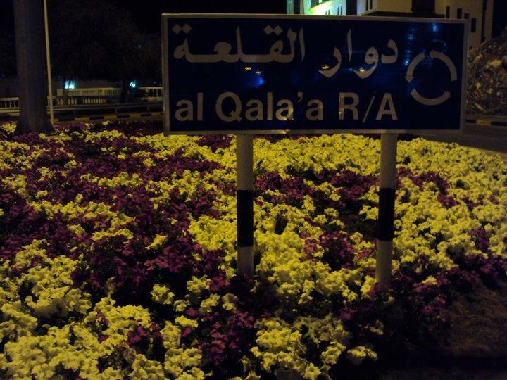 Señal de tránsito con las flores que adornan todo Mascate