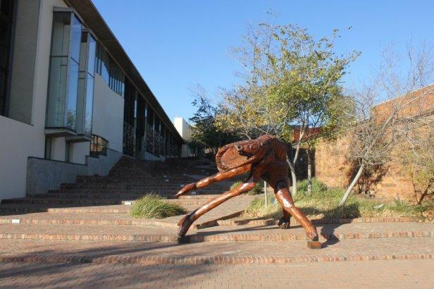 """El pasaje se llama """"La caminata de los derechos"""". A la izquierda el edificio de la Corte Constitucional de Sudáfrica y en sus paredes hay inscripciones con todos los derechos consagrados en la Constitución. El monstruo representa el pasado oscuro del país y se opone a la luz y la libertad que están arriba de las escaleras."""