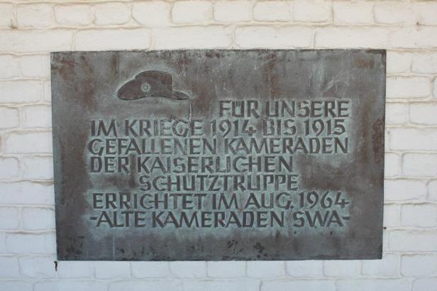 Algo así como: A nuestros compañeros muertos en las guerras de 1914 y 1915 para proteger el imperio. Establecido en 1964. Altos camaradas de África del Sudoeste.