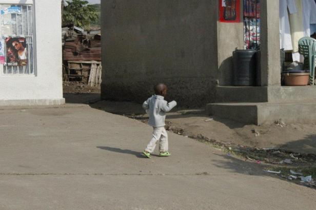 Un niño ugandés en las localidades al lado de la carretera