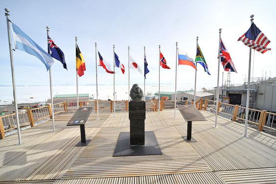 Estatua del británico Archibald McMurdo con las banderas de los países firmantes del Tratado Antártico (Fuente)