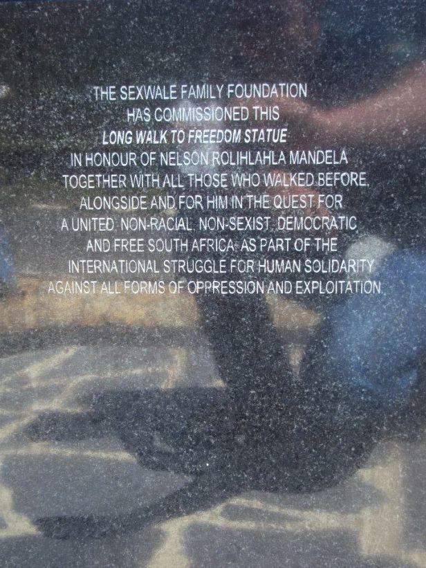 Texto en el costado de la estatua de Nelson Mandela en la Prisión Víctor Vorster en Paarl, Sudáfrica